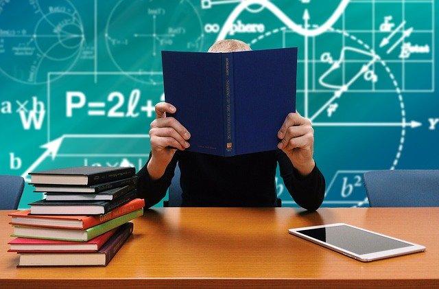 Persona che legge, libri sulla scrivania e lavagna con formule matematiche.